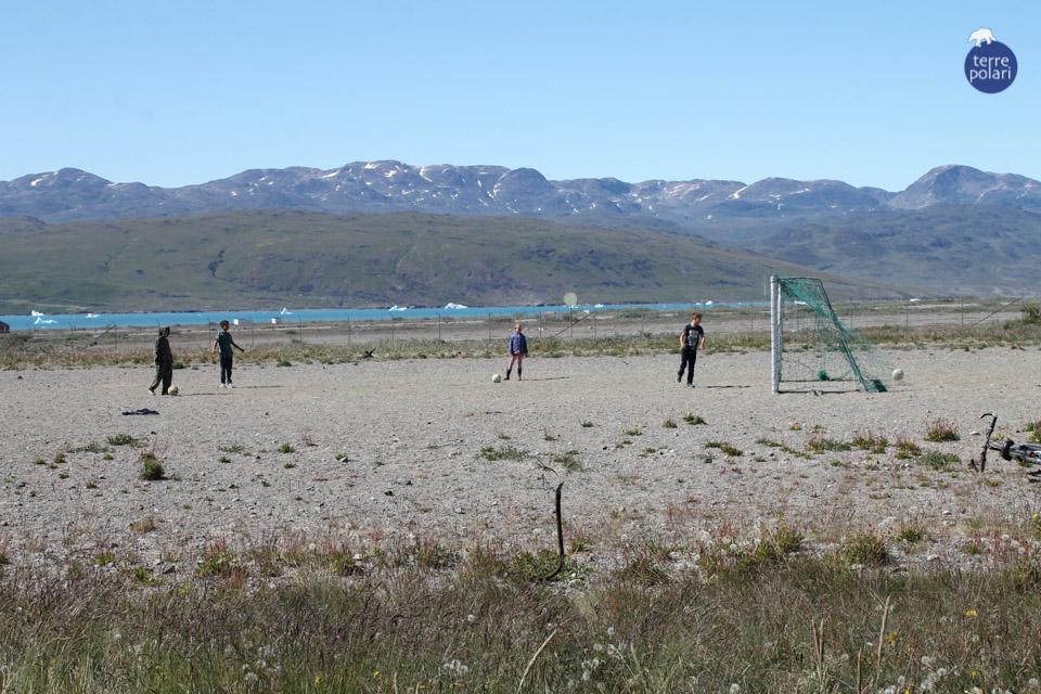 """FOTO 1 PARTITA IN GROENLANDIA_BELTRACCHINI 1 -AUTORE Mauro Beltracchini -viaggio Kayak e trekking 15 giorni in Groenlandia, gruppo internazionale 15-31 Luglio 2014 Descrizione foto -Arrivo in Groenlandia: l'emozione è forte, siamo appena atterrati; il volo è trascorso tranquillo con ottima visibiltà sulla calotta polare, sui nunatak e sui laghi sopraglaciali; avventuroso l'atterraggio nel fiordo a pochi metri dalla lingua glaciale: atterriamo a Narsarsuaq, il sole è intenso e scalda, i colori sembrano quelli del mediterraneo, i bambini giocano a calcio in maglietta a maniche corte, ….ma qualcosa di irreale ci circonda e ci confonde le idee: sarà il fuso orario?....No! dietro di loro nel fiordo già si scorgono i primi Iceberg! Chissà cosa succede se perdono il pallone nel fiordo….È solo l'inizio di una grande avventura ai confini del mondo. Categoria foto Foto """"più divertente"""""""