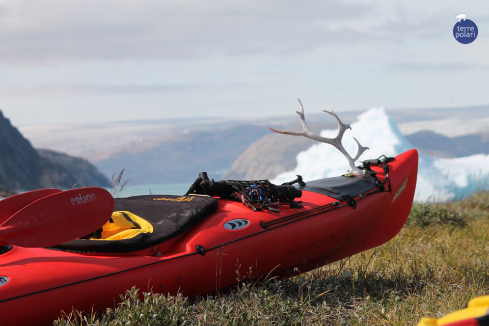 """FOTO 2 kayak personalizzato_BELTRACCHINI 2 -AUTORE Mauro Beltracchini -viaggio Kayak 15 giorni in Groenlandia, gruppo internazionale 15-31 Luglio 2014 Descrizione foto -Stiamo pagaiando ormai da quasi una settimana da un fiordo all'altro. Improvvisamente si apre di fronte a noi uno scorcio mozzafiato della calotta polare, manca poco ormai prima di potervi mettere piede. Un paio di giorni e toccheremo con le mani il ghiaccio antico. Passiamo la notte piantando la tenda """"con vista"""" sulla calotta, l'alloggio a dieci stelle del pianeta. Dalla tenda si scorge un Iceberg che galleggia a pochi metri da noi, sullo sfondo la calotta polare, a pochi metri riposa parcheggiato il mio kayak, già personalizzato con un palco di Caribù, reperto naturalistico che mi ha fatto compagnia fino alla fine.  Categoria foto - Foto """"spirito di esplorazione"""""""